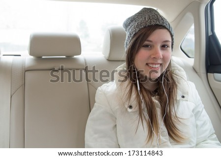 Cute teenage girl with hat and earbuds in backseat of car