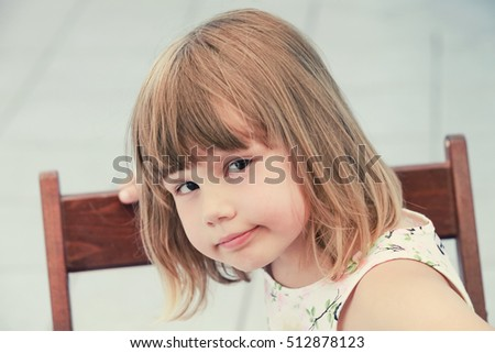 Cute thinking Caucasian little girl, close-up outdoor portrait, vintage toned photo, old instagram style effect