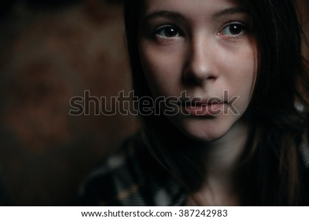 Cute thoughtful young woman. Close up portrait in cold  tones.