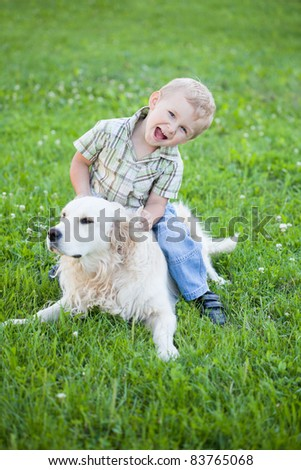 Cute toddler blonde boy with golden retriever hugging close up
