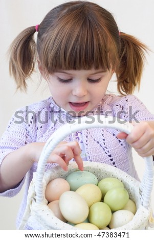 Cute toddler girl holding a basket of Easter eggs