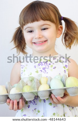 Cute toddler girl holding a carton of Easter eggs