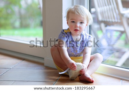Cute toddler girl with blonde curly hair putting on her shoe sitting on the tiles floor next to a big sliding door window with garden view getting ready to play outdoors