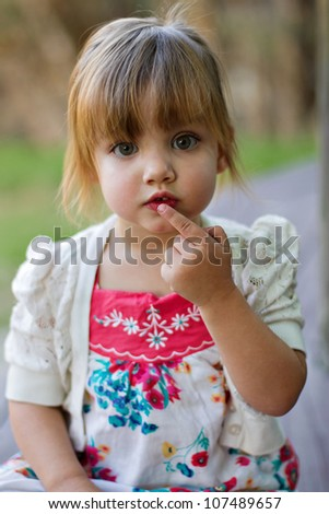 Cute toddler portrait in outdoor park saying be quiet looking into the camera. Shallow depth of field focusing on eyes and face.