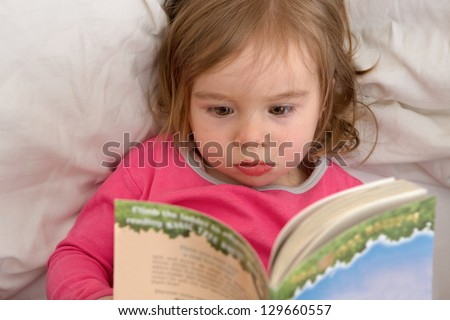 Cute toddler reading her stories before she goes to sleep. Reading habits starts with early age.