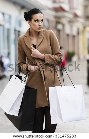 cute young brunette , in coat going for shop in winter time, she is carrying some shopping bag.