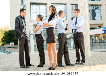 Cute young businesswoman with her team young business people standing in front of office building.