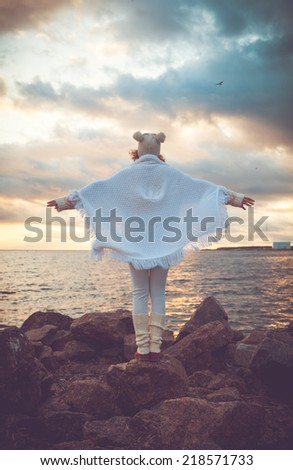 Cute young european woman in knitted clothes on the beach at sunset