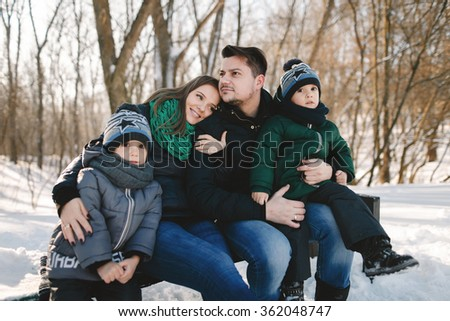 Cute young family with twins and pregnant young mother having fun in winter park on a bright day hugging each other and smiling