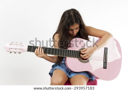 Cute young girl playing guitar and sing .