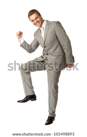 Cute young guy in suit clenching his fist in triumph, isolated over white, success concept