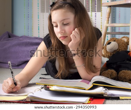 Cute young teenage girl surrounded by books doing homework in her bedroom.