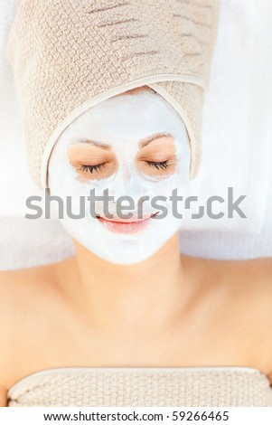 Cute young woman with closed eyes having white cream on her face lying in a spa center