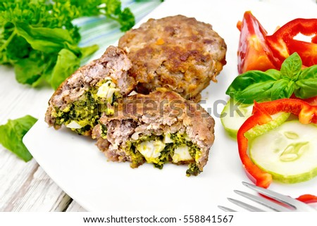 Cutlets stuffed with spinach and egg, salad with tomatoes, cucumber and pepper in a dish on a towel, basil and parsley on the background light wooden boards