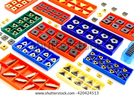 cutters in colorful boxes, metal and golden lathe tools for heavy industry on white background
