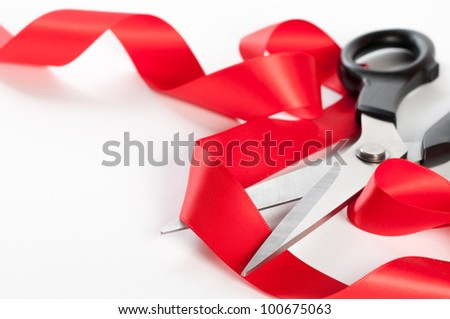 Cutting red ribbon with scissors on a white background