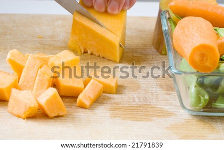 cutting vegetables on a wooden board with knife