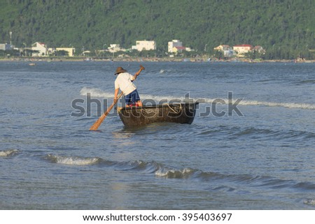 DA NANG, VIETNAM - JANUARY 04, 2016: A fisherman on a traditional Vietnamese round boat in the sea