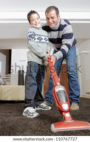 Dad and son vacuum cleaning their living room, smiling and bonding.