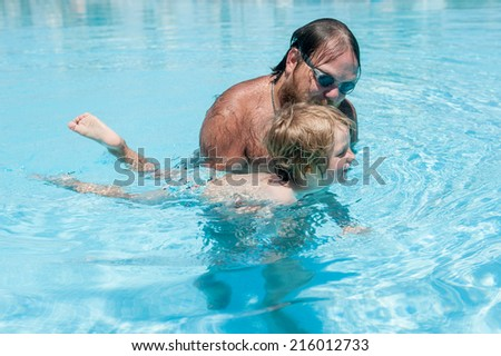 Dad with a son swimming in the pool