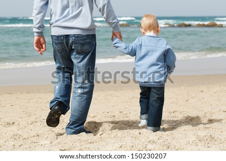 Dad with little boy outdoors at sea