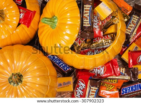 DALLAS, TX - OCTOBER 31, 2014: Decorative pumpkins filled with assorted Halloween chocolate candy made by Mars, Incorporated and the Hershey Company.
