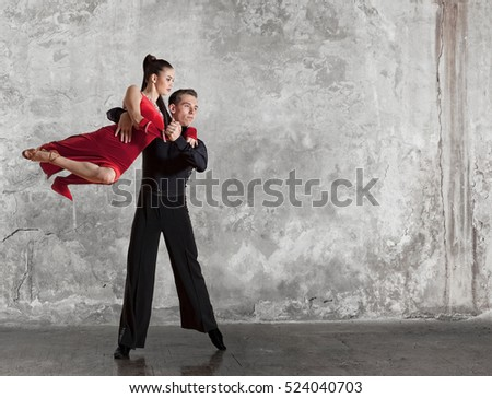 Dance beautiful couple dancing ballroom dancing on wall background. Toned image