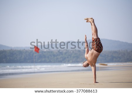 dancer posing on the sandy sea coast