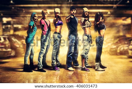 Dancer team pointing handsign to camera. Urban underground parking interior with light explosion effect.