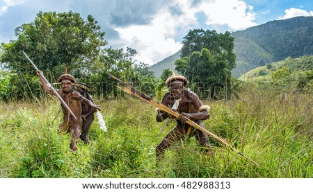 DANI VILLAGE, WAMENA, IRIAN JAYA, NEW GUINEA, INDONESIA - JUNE 6:The attack of the armed group of Papuans. Attacking Group  Warriors of Dani tribe. June 6, 2016, New Guinea Island.