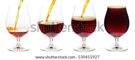 Dark ale or porter beer is pouring into snifter glass isolated on white background