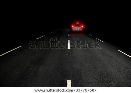 Dark asphalt road and car with red rear lights