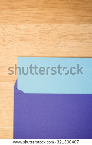dark blue envelope and blue writing paper on a natural wood surface with copy space