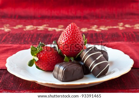 Dark chocolate bon-bons and strawberries on a white fine china plate with gold decoration on the rim. Red textured background.