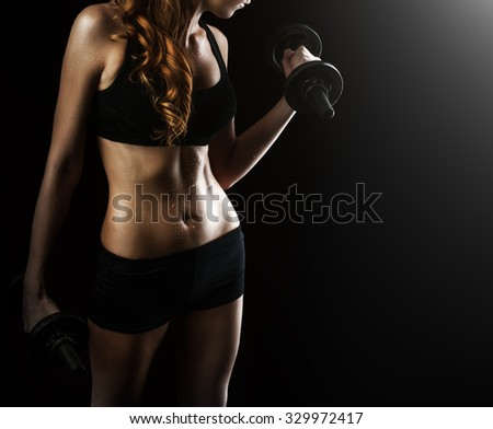 Dark contrast photo of young beautiful fitness woman with beads of sweat which training in gym. Working out with dumbbells on black background