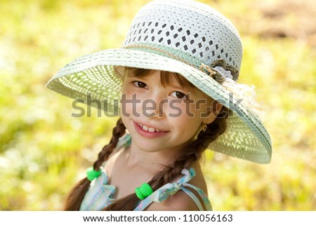 Dark-haired girl in a hat and summer dress