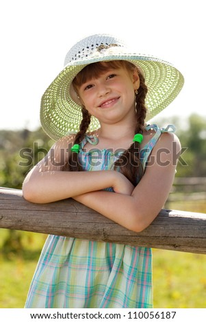 Dark-haired girl in a wicker hat with braids