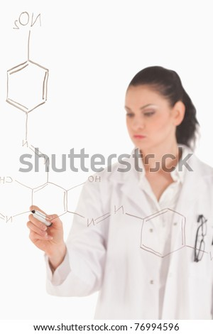 Dark-haired scientist writing a formula on a white board in a lab