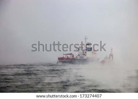 Dark image of ship and boats on sea during a violent blizzard.