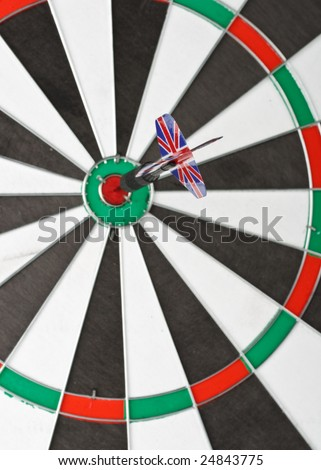 Dart on bull's eye of a dartboard. Close up. Selective focus.