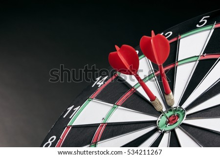 Darts arrows hitting the target center on a dark background