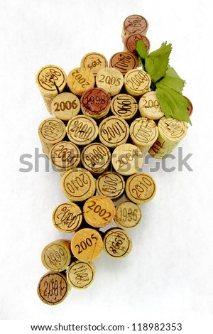 Dated and vintage wine corks in the shape of a group of grapes with a green leaf on white background.