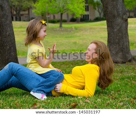 Daughter and mother playing counting lying on park lawn