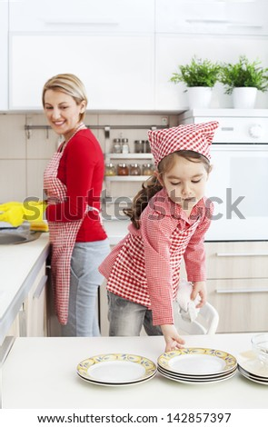 Dauhter helping her mother with dishwashing in the kitchen