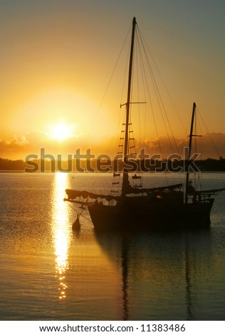Daybreak through clouds over an old ketch.