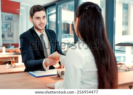 Deal. Rear image of beautiful young woman in formalwear shaking hands with her business partner while sitting at the restaurant