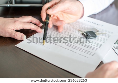 Dealer showing the signature place of a contract with his pen