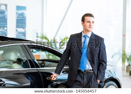 dealer stands near a new car in the showroom, put one hand on the car