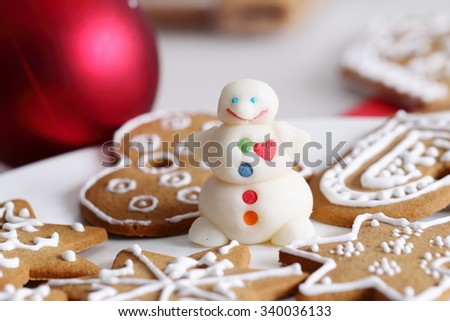 Decorated christmas sugar snowman and gingerbread cookies and edcorations on the table.
