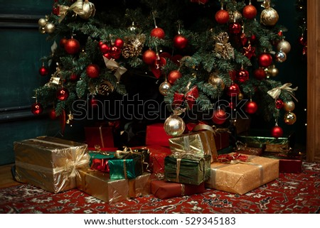 Decorated Christmas tree closeup. Colorful gifts and presents under a beautiful christmas tree